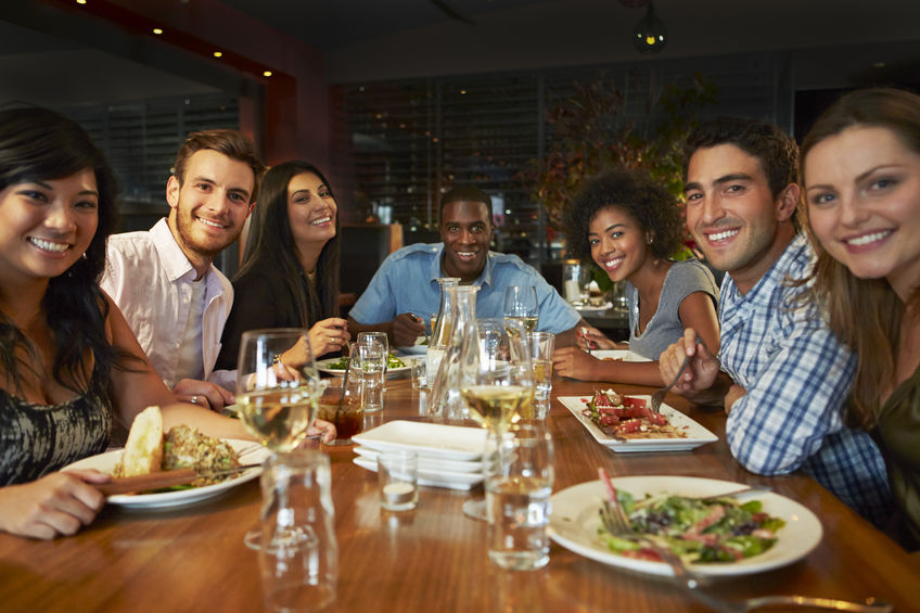 31021423 - group of friends enjoying meal in restaurant